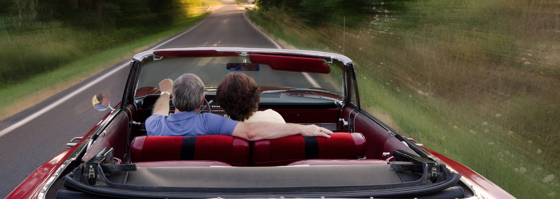 couple riding in convertable car driving down road
